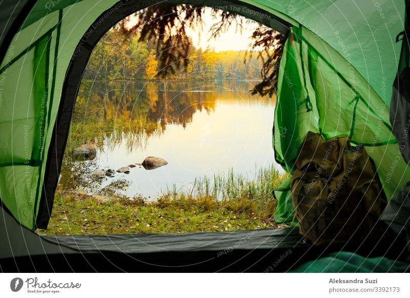 View from inside a tourist tent with backpack. Beautiful Scandinavian landscape of forest and lake. Finland active activity adventure autumn beautiful camp