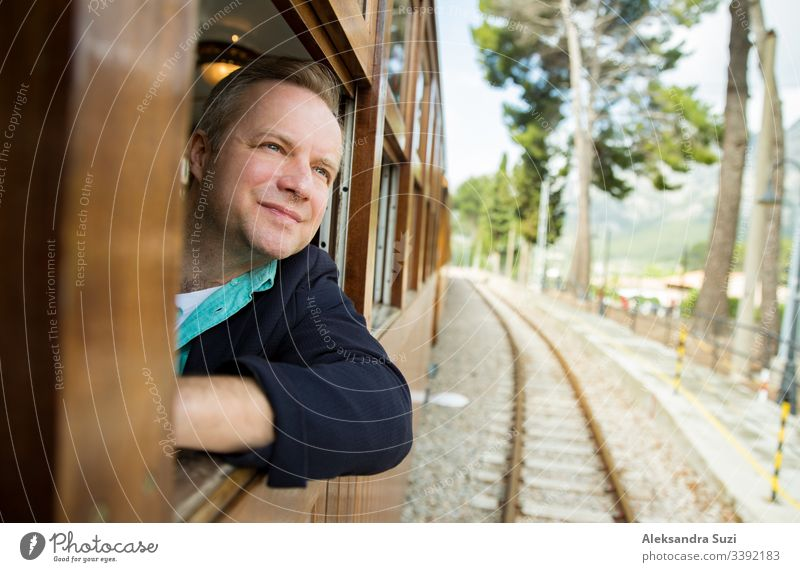 Man traveling by retro wooden train, looking through the window. Beautiful landscape of mountains. Majorca, Spain. adventure alone beautiful blond cheerful