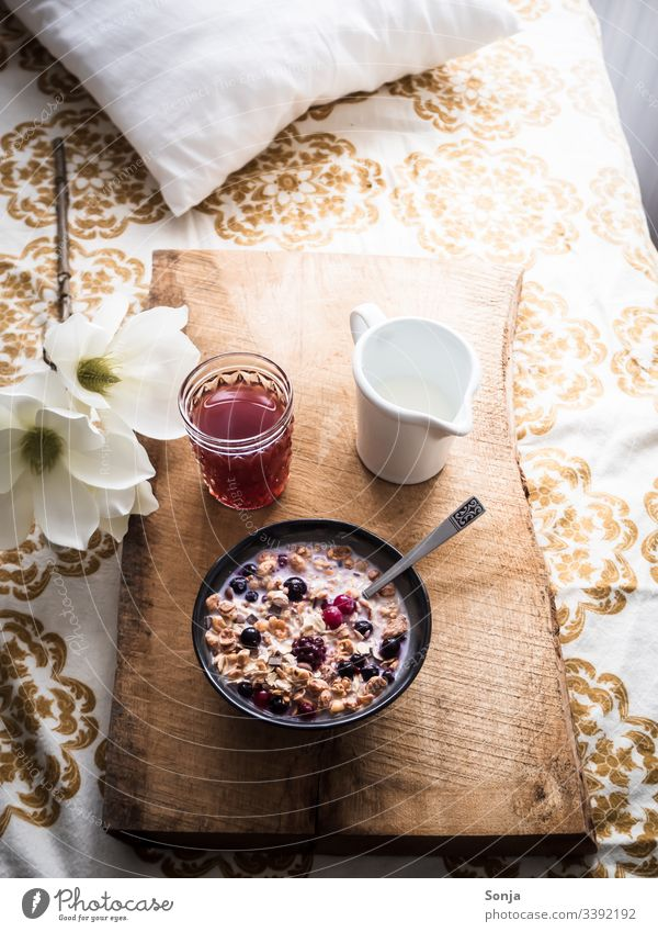 Romantic breakfast with muesli, milk and fresh berries on a wooden serving tray in bed Breakfast Milk raspberry blueberry Bed Retro Wooden board Spoon