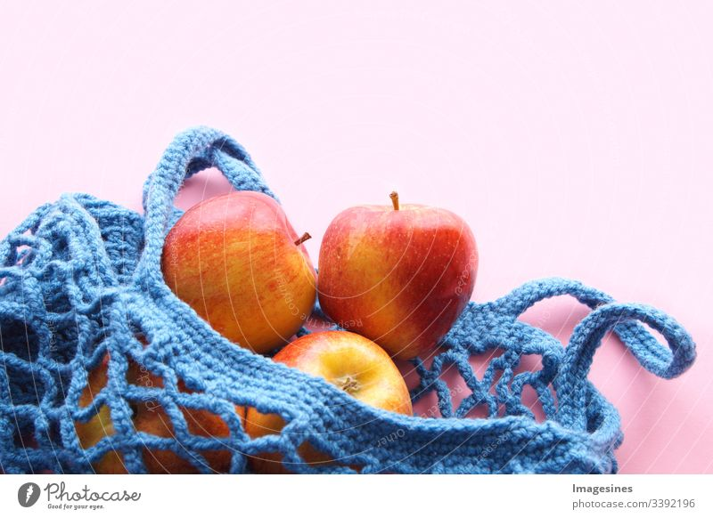 Shopping net made of cotton - Free of plastic. Reusable shopping bag with fruit - apples on pink background. Zero waste and ecology concept. environmentally friendly buyer. top view