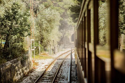 Retro wooden train traveling along railroad in mountains. Beautiful sunny summer landscape. Majorca, Spain. adventure beautiful commuter countryside destination