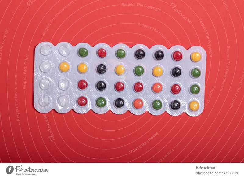 Colourful pills on red background medicine Medicine Close-up Healthy Medical treatment candy Chewing gum drug variegated Red Dragee tablets Pharmaceutics