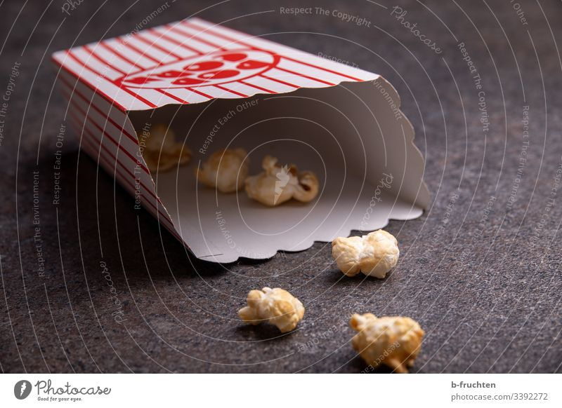 Some popcorn in a bag on the floor Popcorn Paper bag Cinema Remainder Interior shot Food Snack Delicious Maize Close-up Fast food Eating Salty Sweet Candy