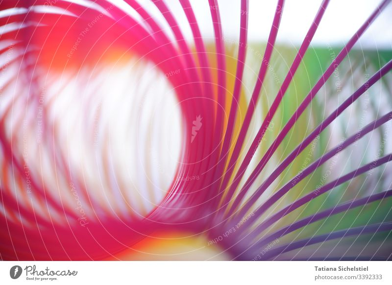 Single spirals of a curved rainbow spiral / stair jumpers Toys spirally variegated Spiral spiral line Multicoloured Colour photo Close-up Blur