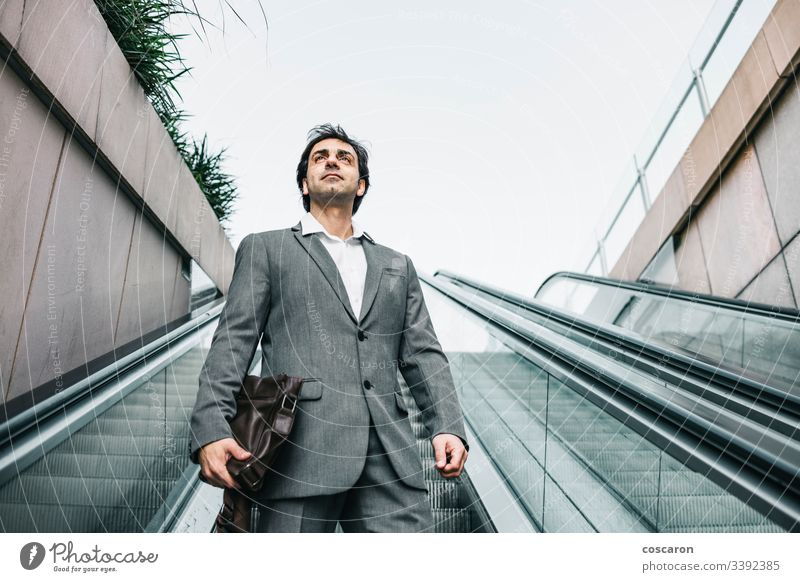 Businessman in a suit riding up an escalator adult airport attractive boss business business people business wear businessman businesspeople city coffee