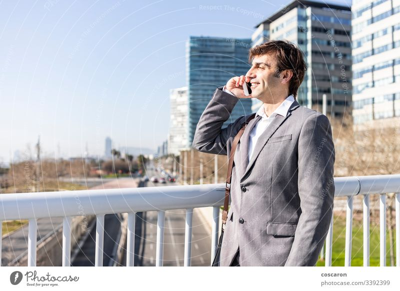 Happy businessman using a cellphone on the city adult barcelona bridge buildings call cityscape copyspace elegant enjoy fun handsome happy job laughing