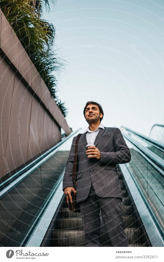 Businessman in a suit drinking a coffee and riding up an escalator adult airport attractive boss business business people business wear businessman