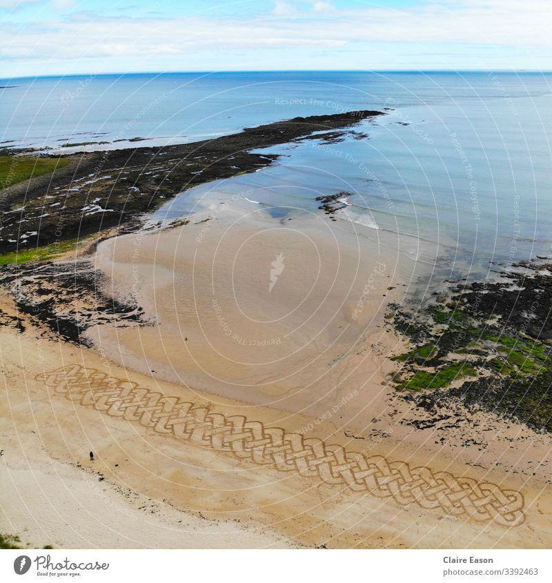 Giant sand art Celtic knot work braid along a beach with a person for scale created by dji camera Celtic design coast sustainable ecotourism environment nature