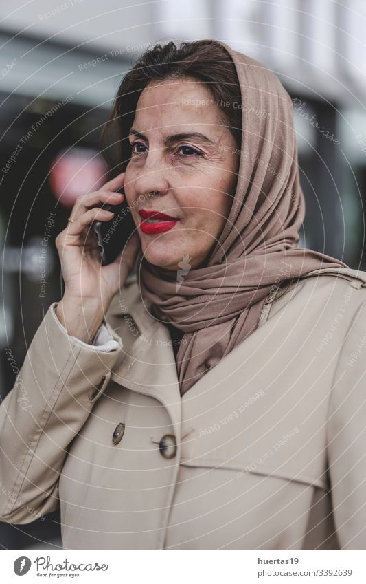 Arab woman with hijab talking on the phone female attractive suitcase muslim muslim woman mobile phone arab baggage travel: islamic traveler arabian arabic trip