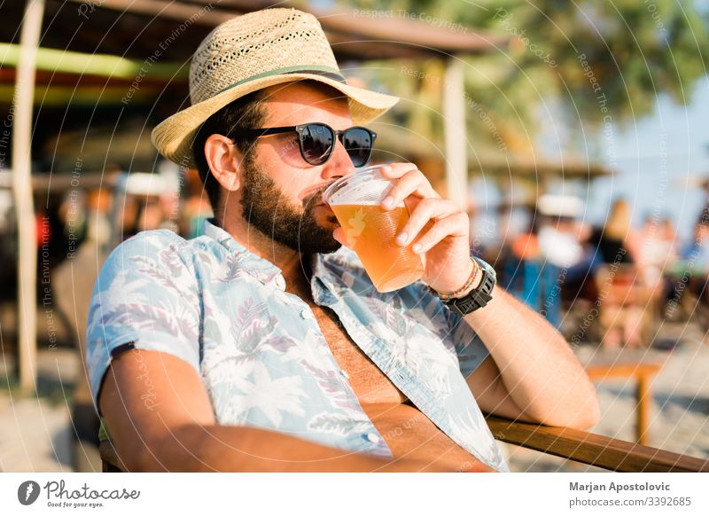 Young man drinking beer a beach bar enjoying sunset 30s adult alcohol alone bearded beverage casual caucasian cheers cool destination fun guy handsome hat