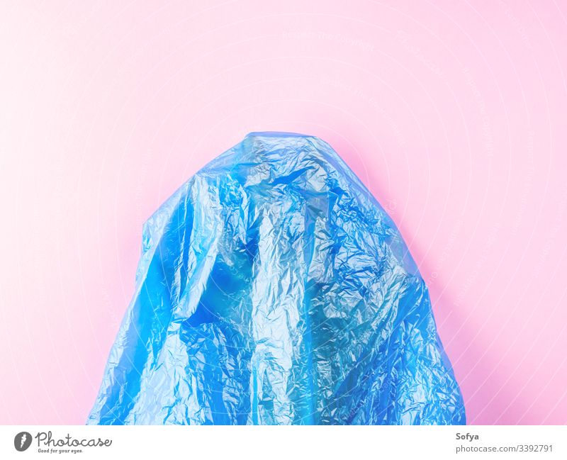 Human hand trapped in plastic bag on pink background. Conceptual flat lay ocean pollution metaphor sea water blue symbol nature plastic free stop help concept