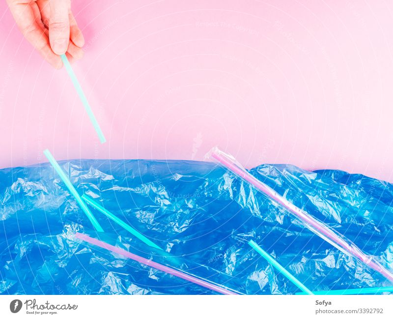 Plastic straws thrown in ocean. Pollution concept. Flat lay on pink background plastic hand pollution metaphor sea water blue flat lay symbol nature bag