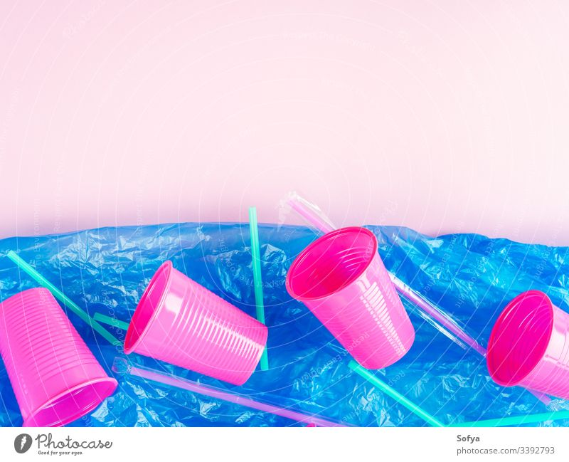 Plastic straws and cups in ocean represented by blue plastic bag. Pollution concept. Flat lay on pink glass disposable floating pollution sea metaphor throw