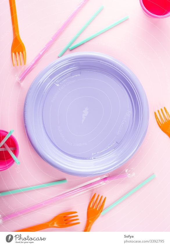 Disposable colorful plastic dish, straws and cups. Pastel and neon colors disposable tableware frame copy space blank plate ban pollution throw pink flat lay