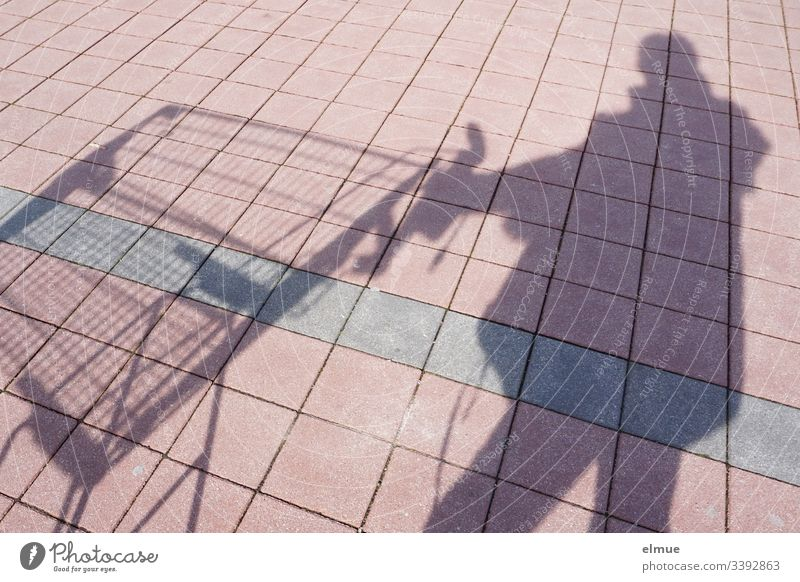 Shadow person with shopping cart Shadow play Shopping Trolley Sunlight Day Deserted Colour photo Parking lot tiles Square Perspective plan surface fun Funny