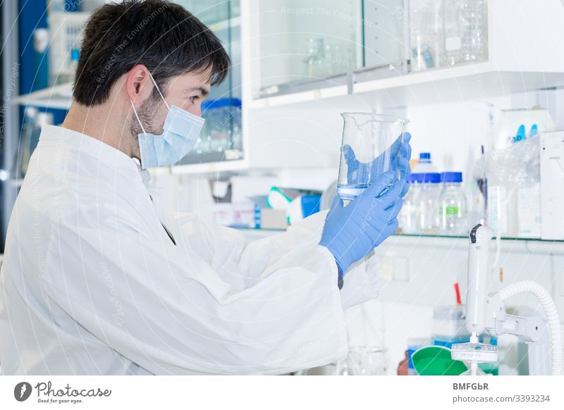 man in laboratory holding a glass an watching the liquid in it analysis analyzing biological biotechnology care chemical chemist chemistry clinic corona