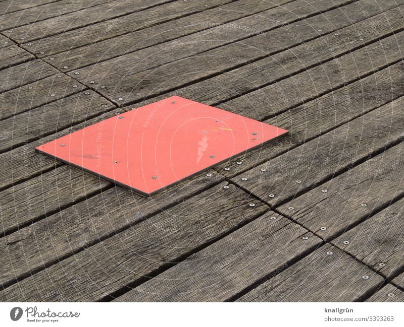 red rectangular cover plate on screwed wooden floor boards Wood Wooden board Red Brown Structures and shapes Deserted Exterior shot Colour photo Day Pattern