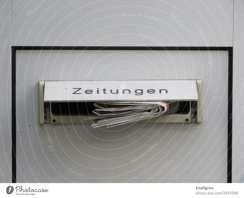 "Daily newspaper in a front door letterbox with the inscription ""Zeitungen steckenend Newspaper Mailbox Mailbox slot House (Residential Structure) Exterior shot"