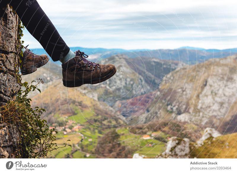 Traveler legs enjoying landscape while sitting on edge of rock against misty highland traveler cliff mountain trekking viewpoint freedom height adventure relax