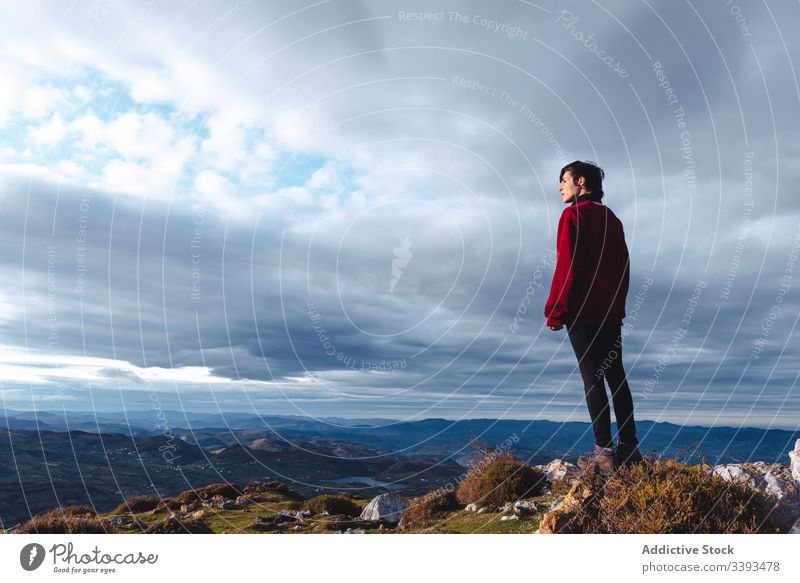 Traveler enjoying freedom while standing on hilltop and observing wide highland woman hike mountain inspiration adventure travel viewpoint trekking hands apart