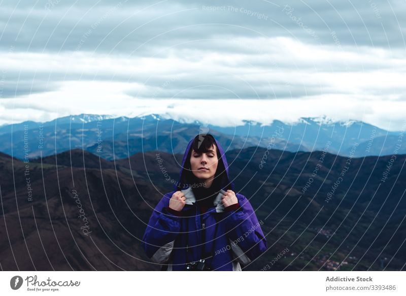 woman tourist in violet jacket with backpack with close eyes in picturesque mountain ridges while standing in Monsacro travel tourism adventure hike highland