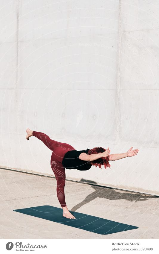 Woman doing balance exercise in tree pose while practicing yoga on street athlete woman practice training stretch barefoot concrete calm fit urban female