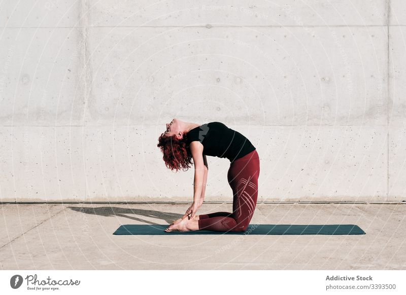 Woman doing yoga in camel pose on street woman stretch practice asana training exercise flexible athlete calm gymnastic concrete urban wellness female wellbeing
