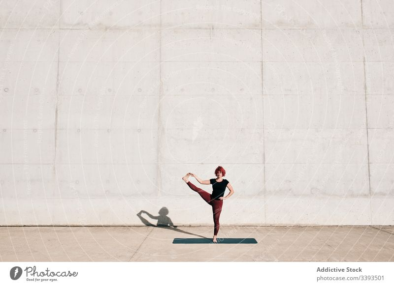 Woman doing extended hand to big toe yoga pose on street woman stretch practice asana training exercise flexible athlete calm gymnastic concrete urban wellness