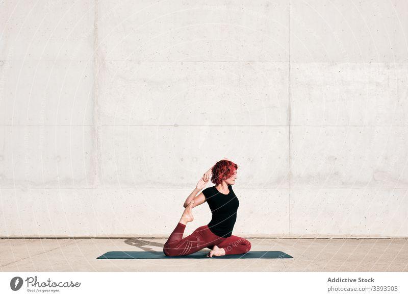 Flexible barefoot woman stretching body in bound swan pose while training on street yoga flexible athlete exercise practice gymnastic badha hamsasana physical