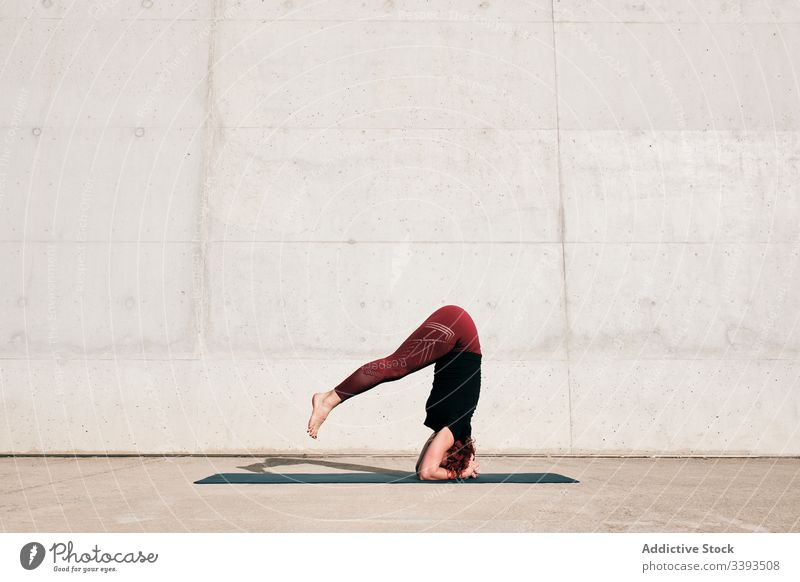 Woman doing balance exercise in headstand pose while practicing yoga on street woman acrobatic practice training urban sirsasana concrete strong flexible