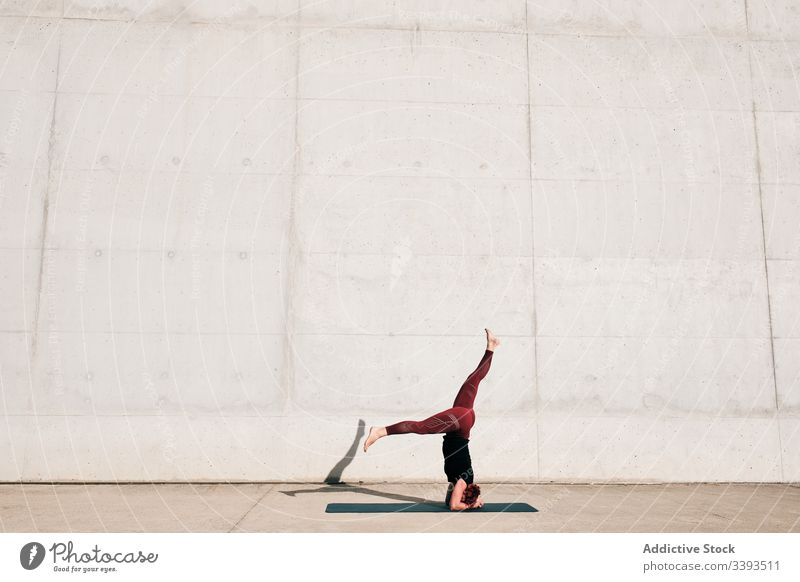 Woman doing balance exercise in headstand with split pose while practicing yoga on street woman acrobatic practice training urban sirsasana concrete strong
