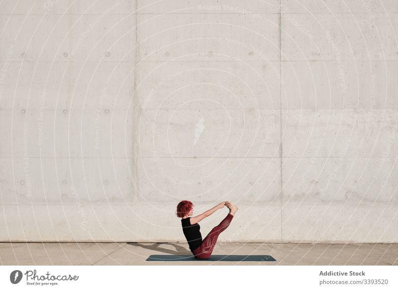 Flexible young sportswoman practicing yoga in balance paripurna navasana on street boat pose flexible exercise stretch acrobatic practice training gymnastic