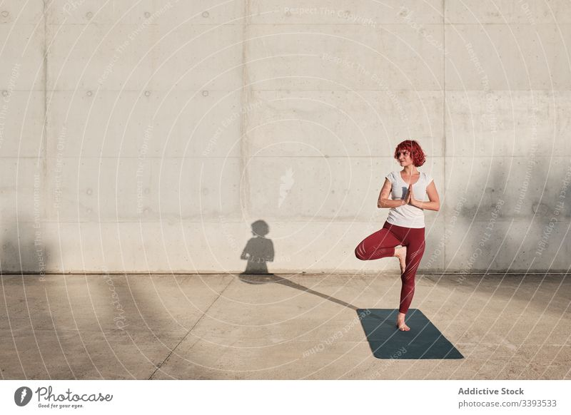 Woman doing balance exercise in tree pose while practicing yoga on street athlete namaste woman meditate practice training stretch barefoot concrete calm