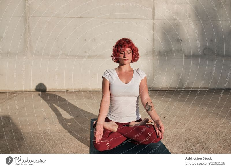 Woman with eyes closed meditating in lotus pose on street during sunset woman meditate yoga tranquil practice gyan mudra flexible idyllic gymnastic athlete