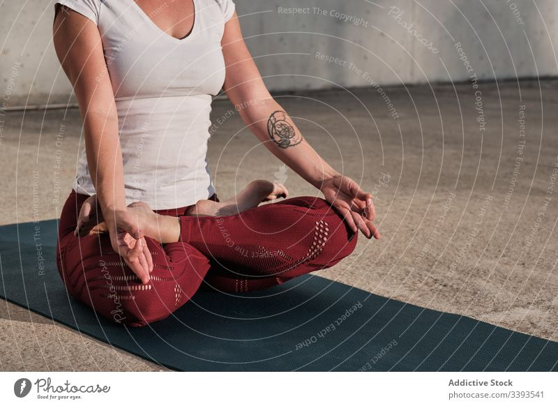 Anonymous woman meditating in lotus pose on street meditate yoga tranquil practice gyan mudra flexible idyllic gymnastic athlete padmasana barefoot concrete