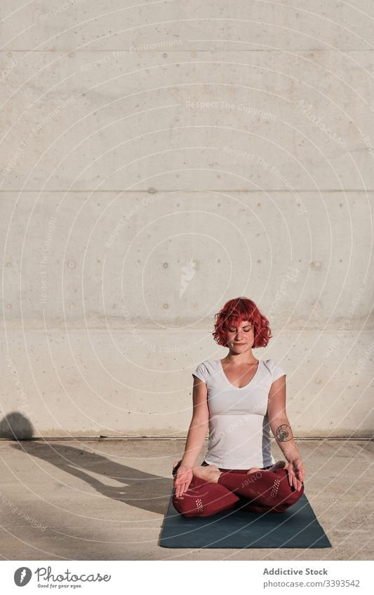 Woman with eyes closed meditating in lotus pose on street during sunset woman meditate yoga tranquil practice gyan mudra flexible idyllic gymnastic athlete