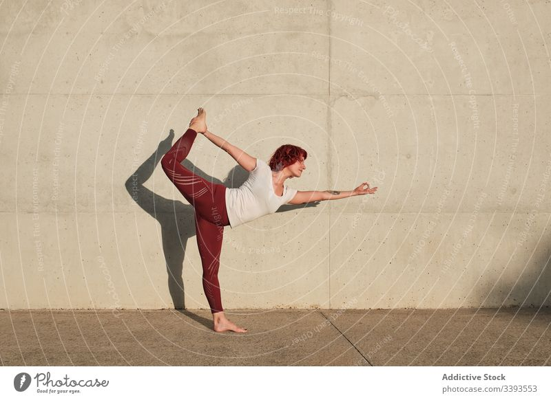 Woman doing yoga in lord of the dance pose on street woman stretch practice asana training exercise flexible athlete calm gymnastic concrete urban wellness