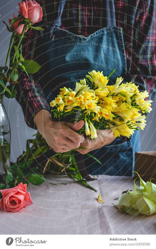 Unrecognizable female professional florist making bouquets. Blooming background owner composition beautiful creative floral craft yellow flowers job workshop
