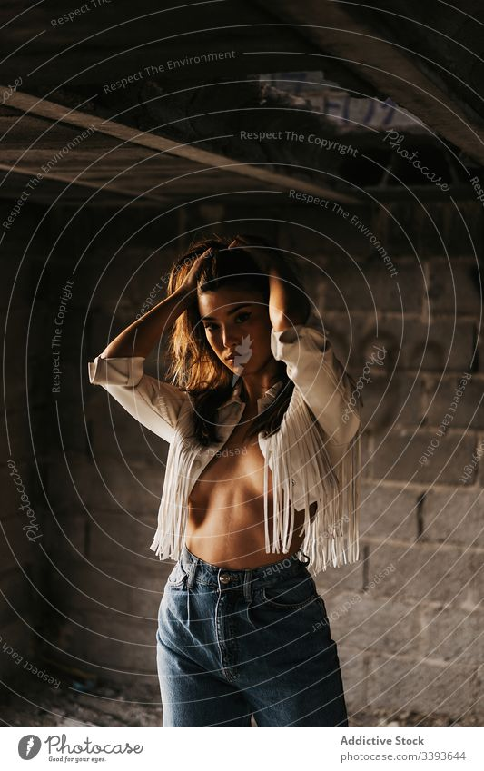 Sensitive young female model inside abandoned building woman topless seductive sensitive grunge sensual touch hair tender brunette jacket naked body appearance
