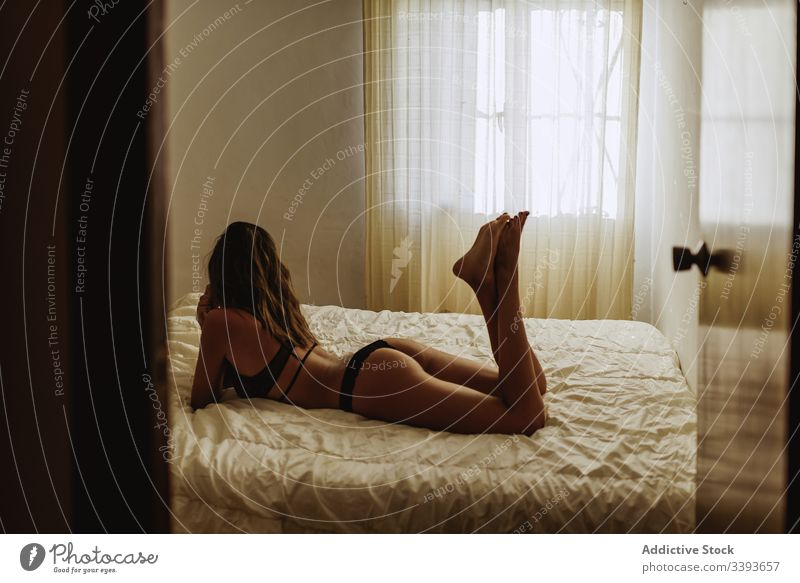 Seductive young woman on bed in morning seductive lying sensual provocative posture sensitive lingerie room slim female feminine tender model temptation passion