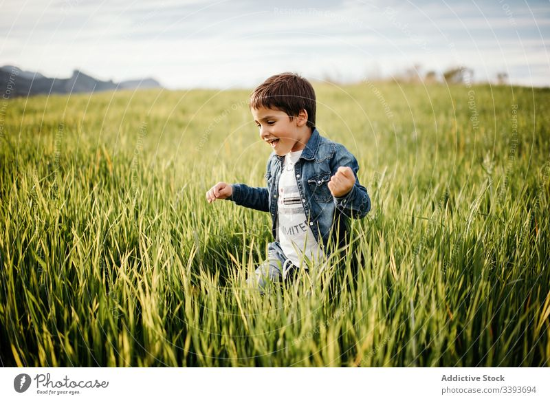 Happy boy enjoying green field in countryside run grass fun happy playful tall rural freedom cloudy walk kid child nature male childhood pleasure peaceful
