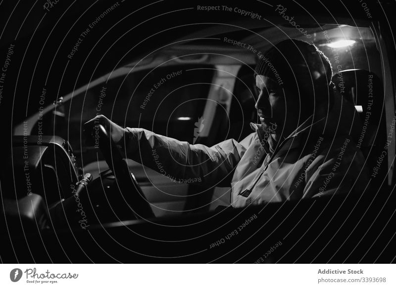 Focused man driving car at night time drive steering wheel focus ride vehicle transport travel auto journey male control road speed modern safety front light