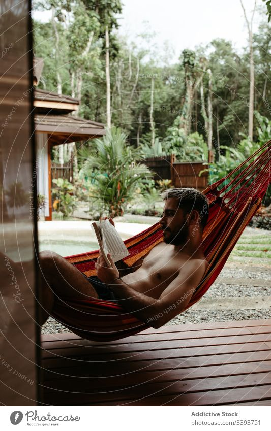 Young male tourist in swimwear with book on hammock man resort hotel lounge chill poolside read exotic tropical swimsuit relax rest sit lifestyle young enjoy
