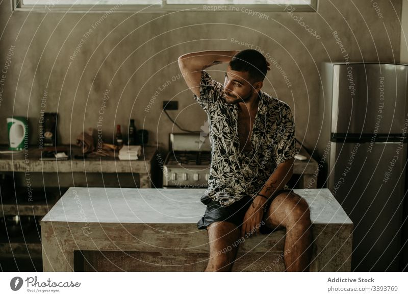 Thoughtful man resting on counter in kitchen thoughtful apartment relax calm domestic morning male contemplate natural dreamy alone serious pensive young