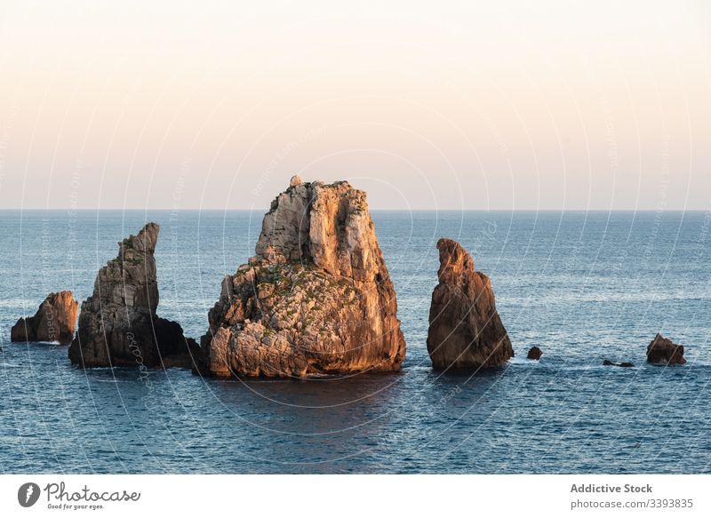 Peaceful landscape of rocky cove in sunset scenery peaceful sea skyline twilight coastline nature water destination tourism seascape cliff stone holiday summer