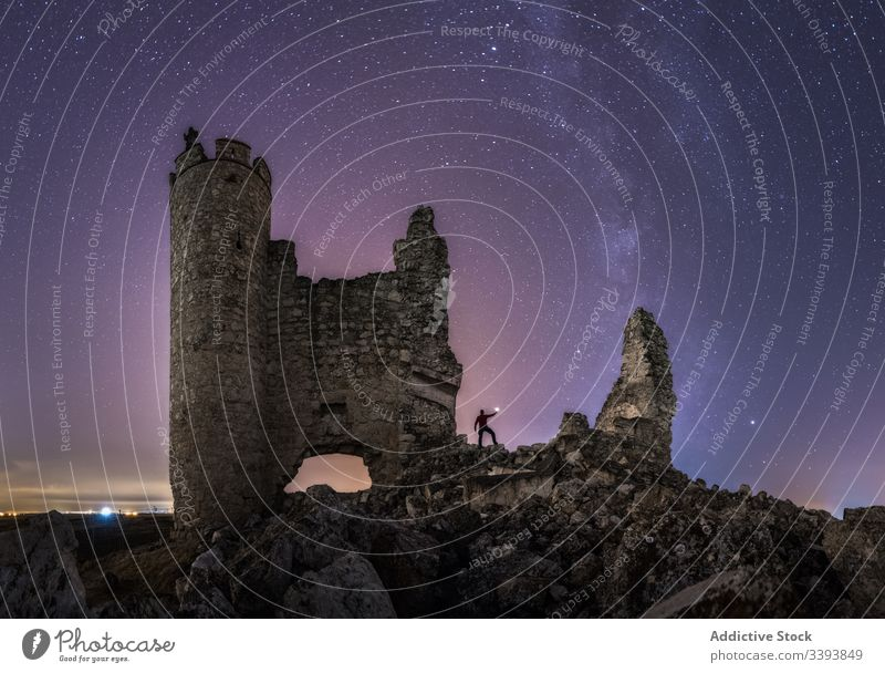 Faceless traveler hiking ruins of castle at night tourist explore ruined lantern sightseeing milky way starry remain old ancient abandoned architecture medieval