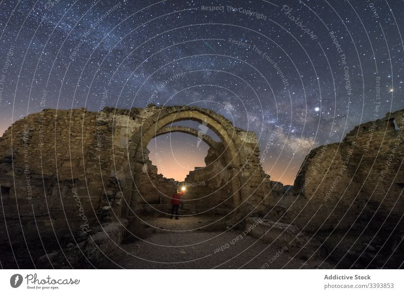 Unrecognizable tourist exploring old ruins at night explore traveler sightseeing remain ancient castle milky way starry abandoned ruined architecture medieval