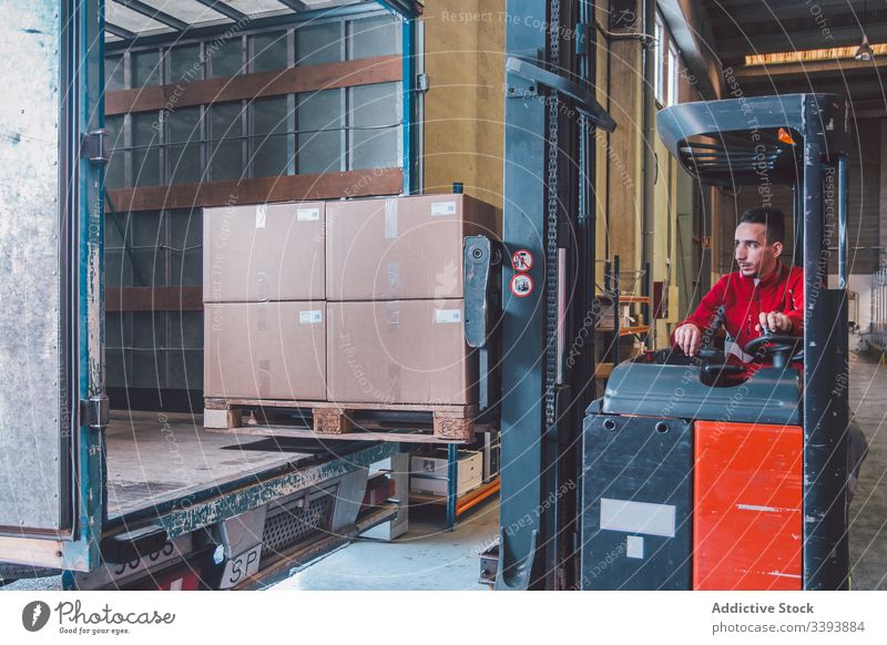 Male worker of logistic company in forklift truck man driver shipment car storage warehouse machine equipment modern operator male service production cargo