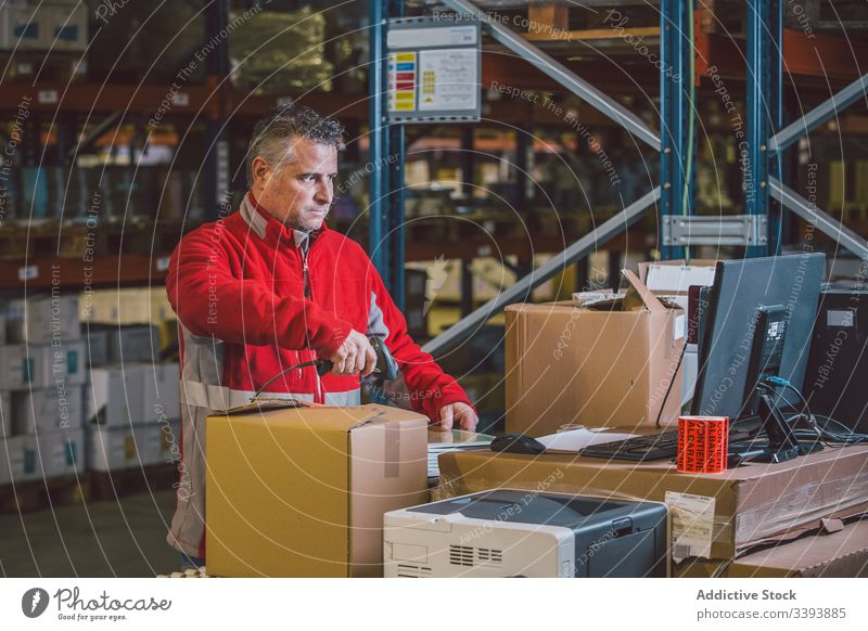 Man scanning packages while working in warehouse logistic service storage male man box job delivery shipment industry professional purchase modern order parcel