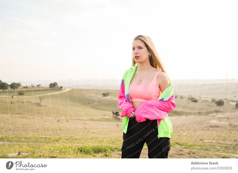 Female hipster in colorful sportswear in countryside woman nature modern blond casual summer individuality style fit cool trendy vivid young athlete female